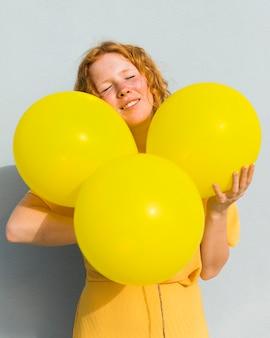 Mittlere schussfrau, die luftballons hält