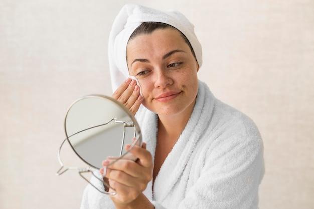 Mittlere schussfrau, die make-up entfernt