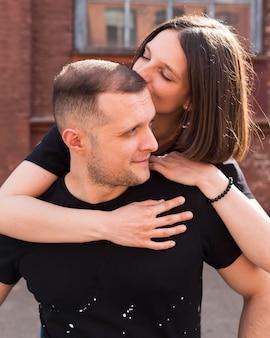 Mittlere schussfrau, die mann auf kopf küsst