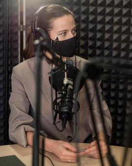 Mittlere schussfrau, die maske am radio trägt
