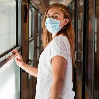 Mittlere schussfrau, die maske im zug trägt