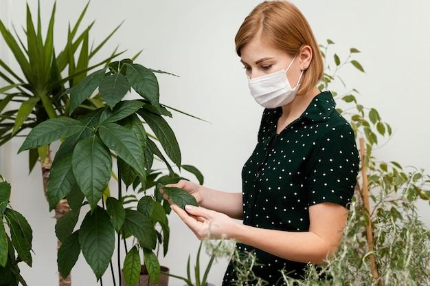 Mittlere schussfrau, die medizinische maske trägt