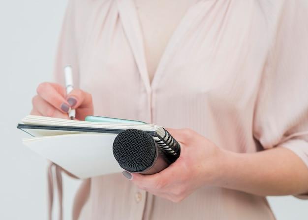 Mittlere schussfrau, die mikrofon hält und notizen schreibt