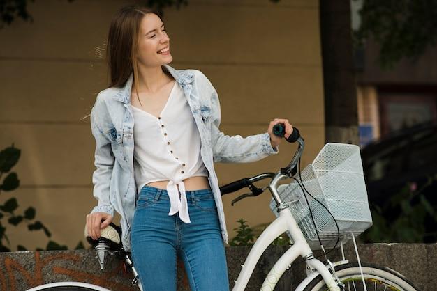 Mittlere schussfrau, die mit fahrrad aufwirft