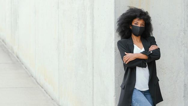 Mittlere schussfrau, die mit gesichtsmaske aufwirft