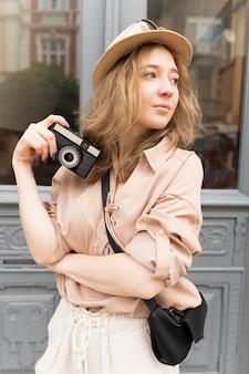 Mittlere schussfrau, die mit kamera aufwirft