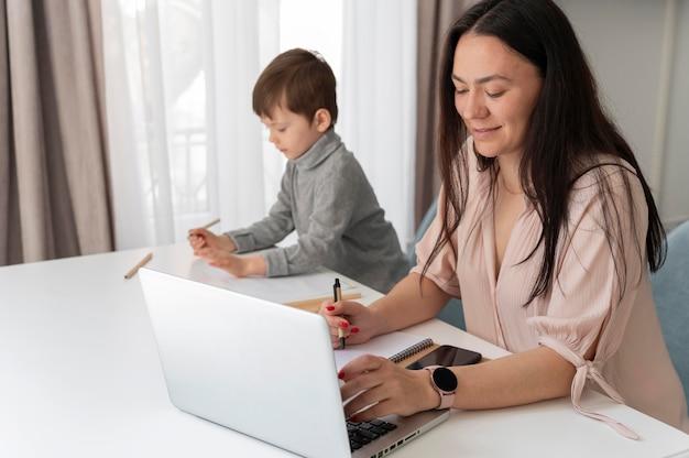 Mittlere schussfrau, die mit laptop arbeitet
