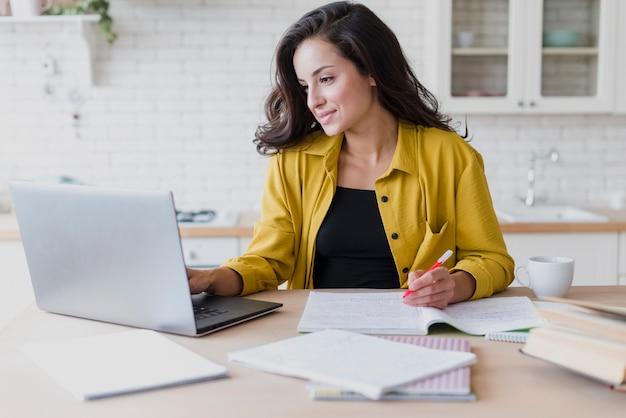 Mittlere schussfrau, die mit laptop studiert