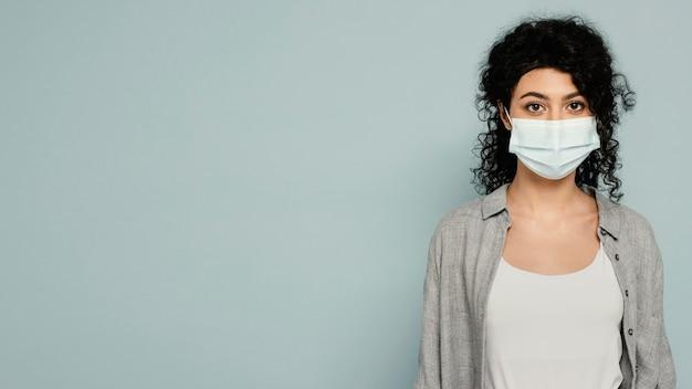 Mittlere schussfrau, die mit maske aufwirft