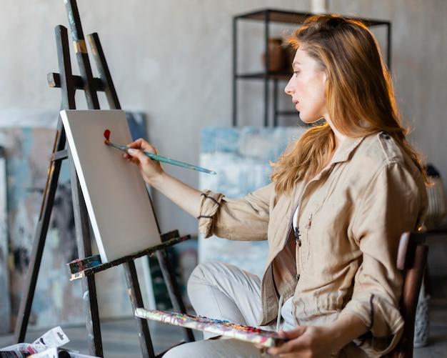 Mittlere schussfrau, die mit pinsel malt