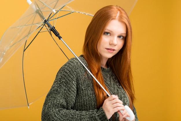 Mittlere schussfrau, die mit regenschirm aufwirft