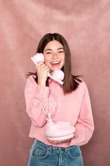 Mittlere schussfrau, die mit rosa telefon aufwirft