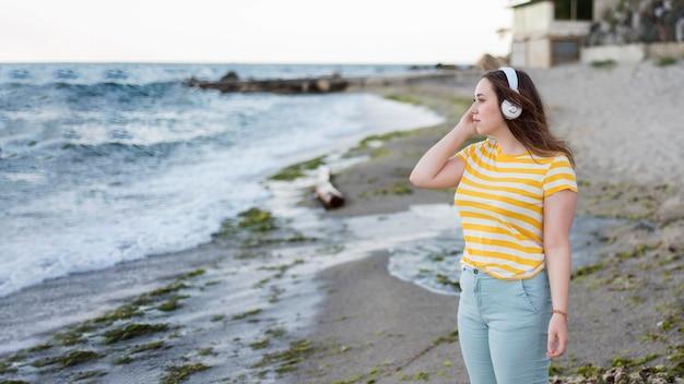 Mittlere schussfrau, die musik am strand hört