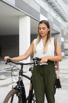 Mittlere schussfrau, die neben fahrrad geht