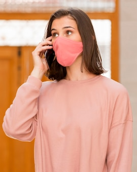 Mittlere schussfrau, die rosa maske trägt