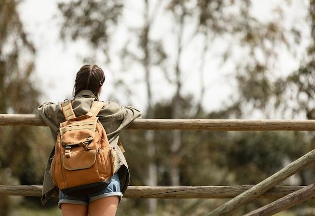 Mittlere schussfrau, die rucksack trägt