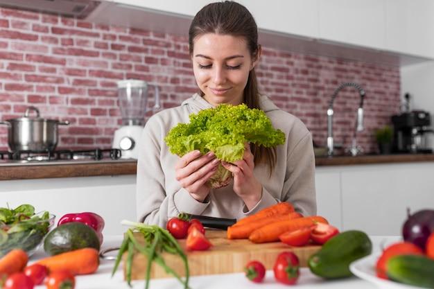 Mittlere schussfrau, die salat hält