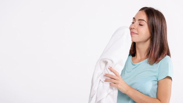 Mittlere schussfrau, die sauberes tuch riecht