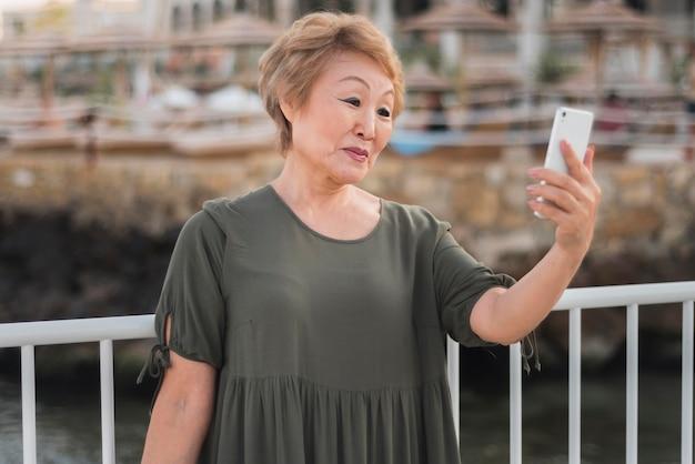 Mittlere schussfrau, die selfie nimmt