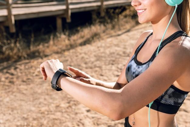 Mittlere schussfrau, die smartwatch am rütteln überprüft