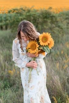 Mittlere schussfrau, die sonnenblumen hält