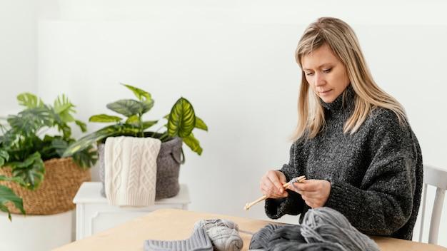 Mittlere schussfrau, die stricknadeln hält