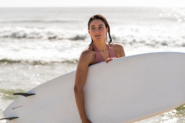 Mittlere schussfrau, die surfbrett hält