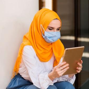 Mittlere schussfrau, die tablette betrachtet