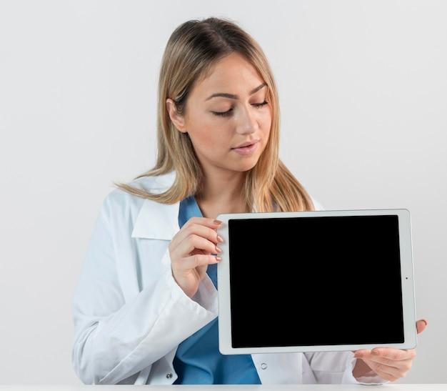 Mittlere schussfrau, die tablette hält