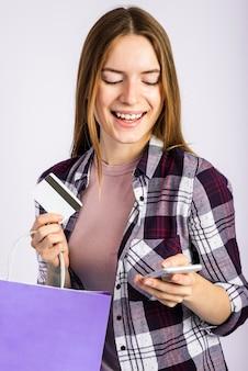 Mittlere schussfrau, die tasche hält und telefon betrachtet