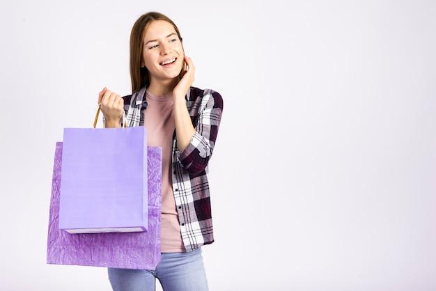 Mittlere schussfrau, die taschen hält und weg schaut