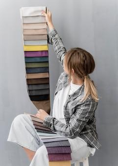 Mittlere schussfrau, die textilien hält Kostenlose Fotos