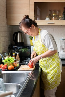 Mittlere schussfrau, die tomate schneidet