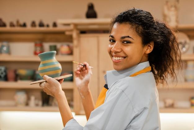 Mittlere schussfrau, die tontopf malt