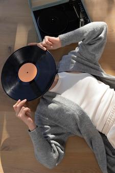 Mittlere schussfrau, die vinyl-draufsicht hält