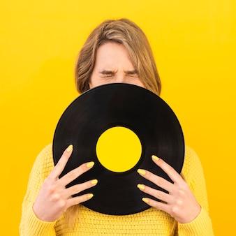 Mittlere schussfrau, die vinyl hält
