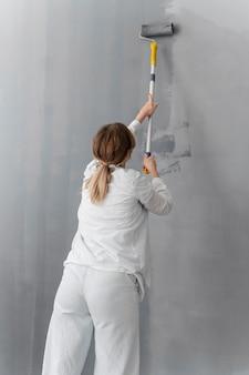 Mittlere schussfrau, die wand malt