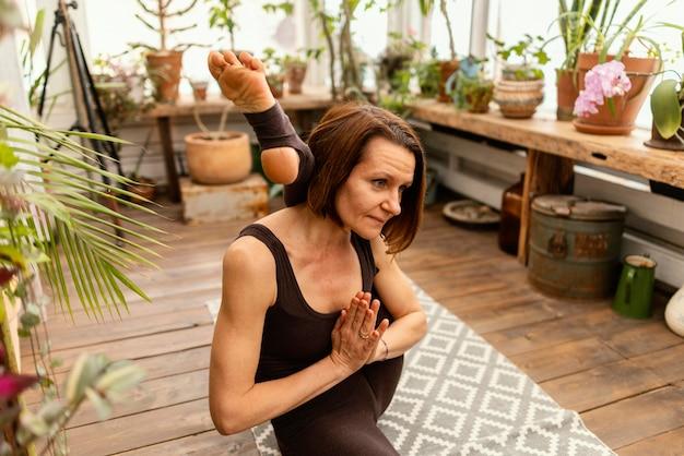 Mittlere schussfrau, die yoga macht