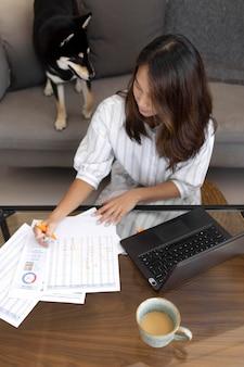 Mittlere schussfrau, die zu hause mit hund arbeitet