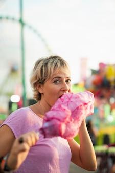Mittlere schussfrau, die zuckerwatte isst