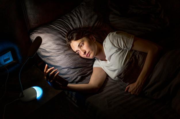 Mittlere schussfrau im bett mit smartphone