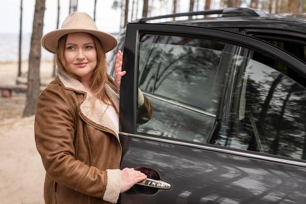 Mittlere schussfrau in der nähe des autos