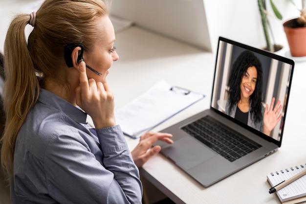 Mittlere schussfrau in der videokonferenz