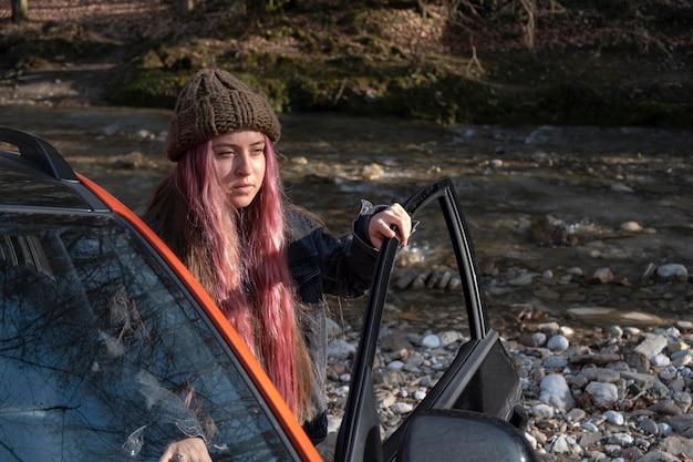 Mittlere schussfrau mit auto im freien