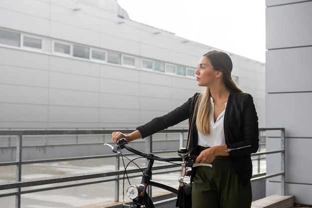 Mittlere schussfrau mit dem fahrrad, das weg schaut