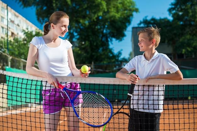 Mittlere schussfrau mit dem kind, das tennis spielt
