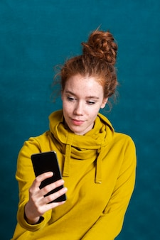 Mittlere schussfrau mit dem smartphone, der ein selfie nimmt