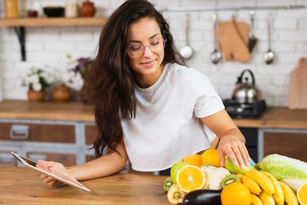Mittlere schussfrau mit früchten und tablette