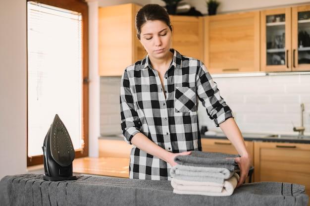 Mittlere schussfrau mit gebügelten handtüchern