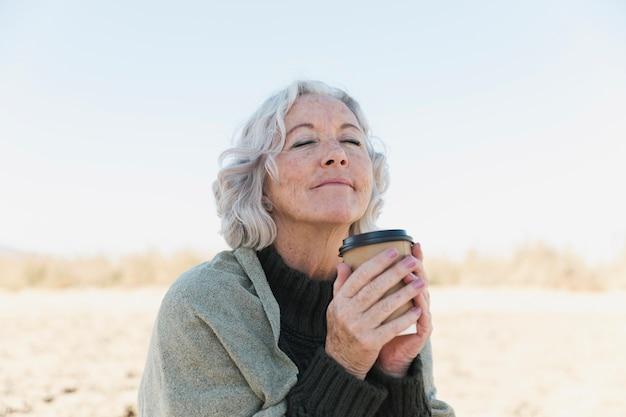 Mittlere schussfrau mit geschlossenen augen und kaffeetasse